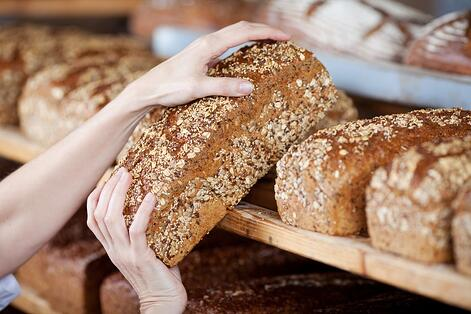 Cropped image of female bakery worker's hands removing whole grain bread loaf from shelves