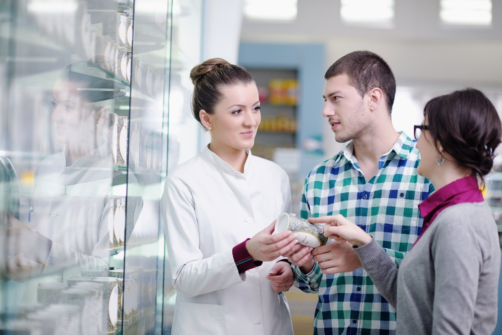young pharmacist suggesting medical drug to buyer in pharmacy drugstore-2